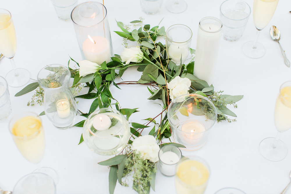 Simple and understated greenery with various candles as centerpieces.