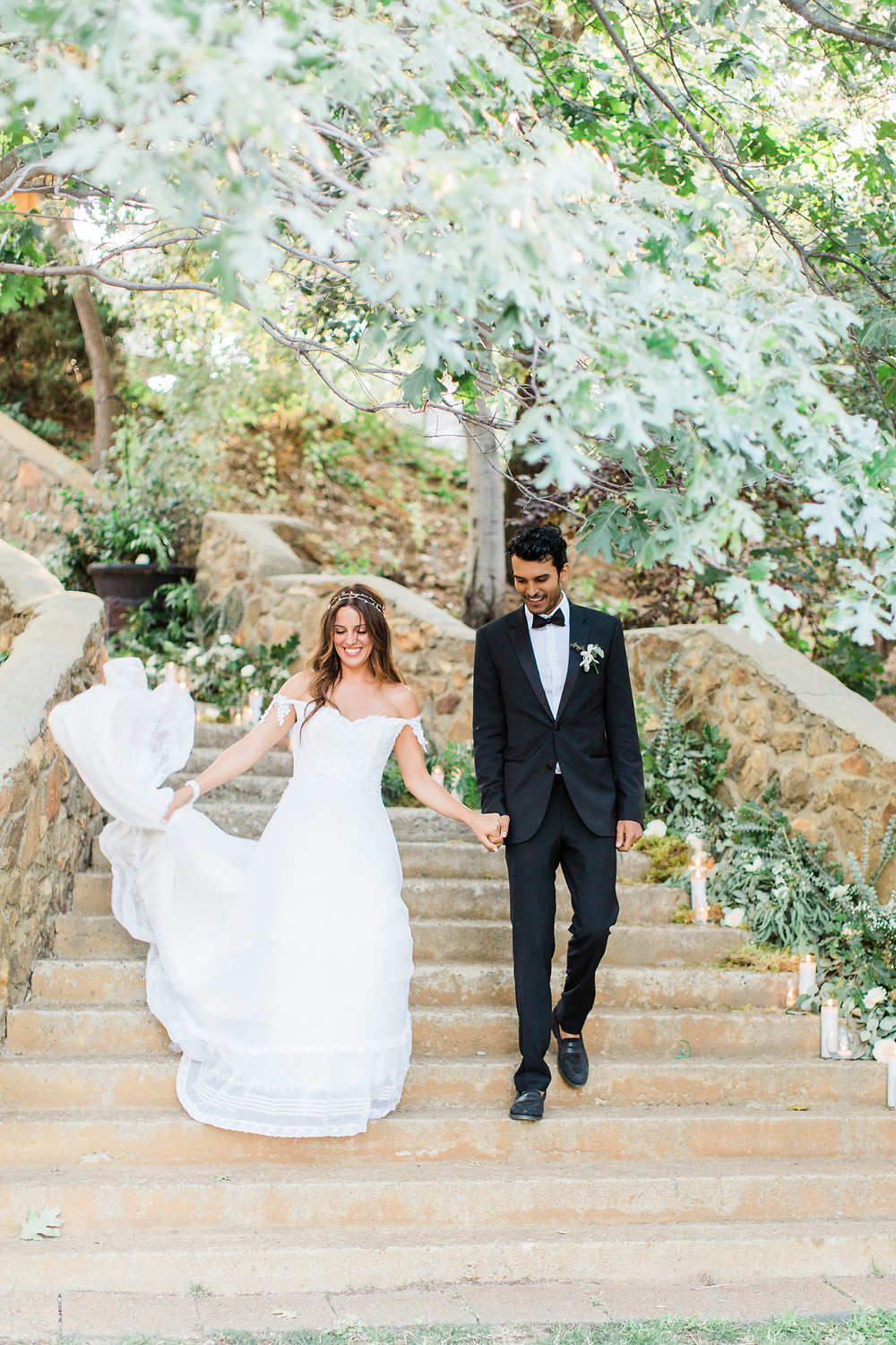 Bride and Groom enter down stone staircase lined with greenery and candles.
