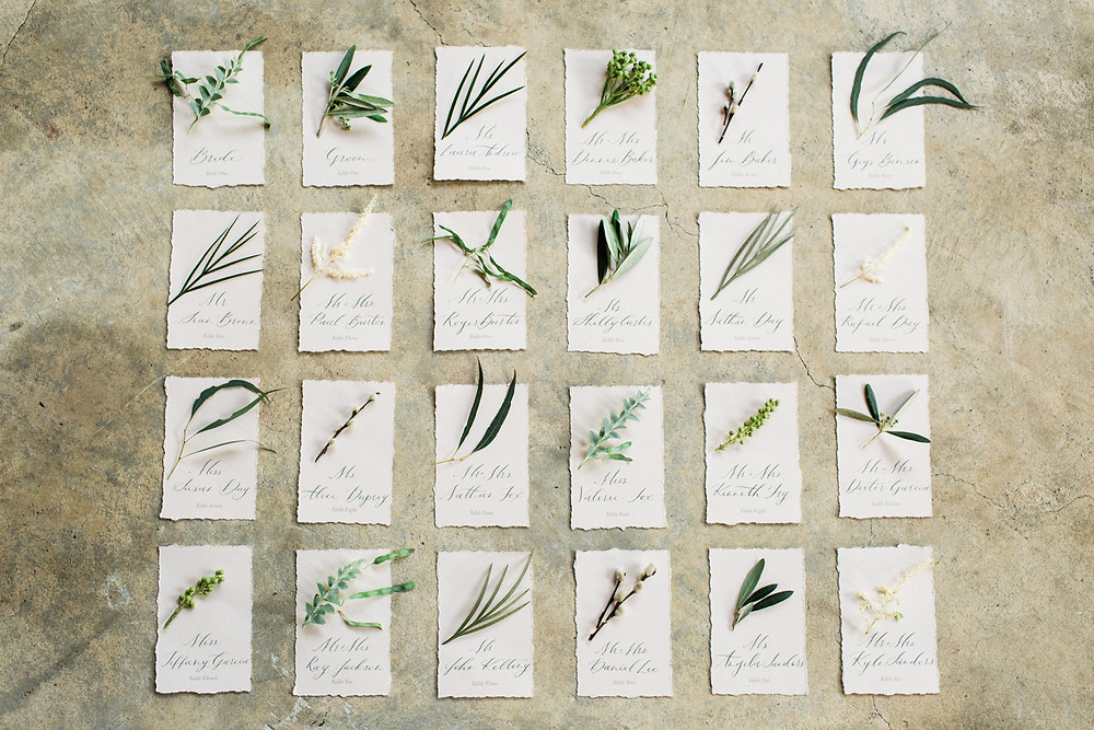 Escort cards paired with snips of greenery