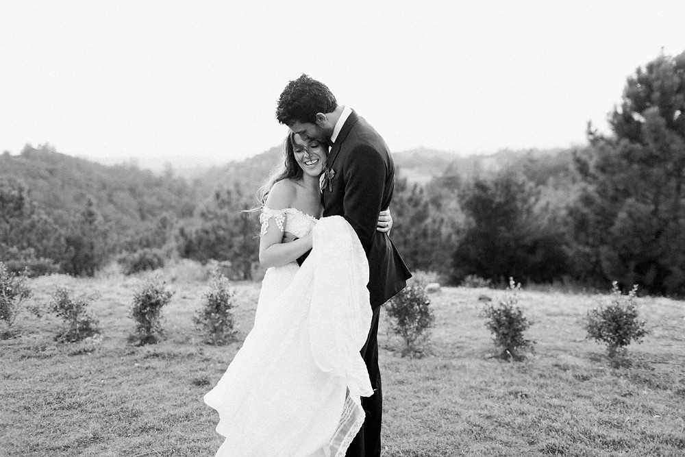 Black and White photo of Bride and Groom embracing at sunset.