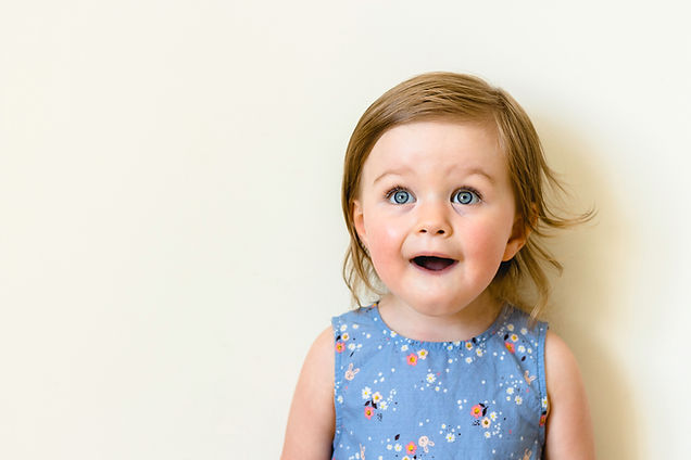 Happy surprised toddler with her mouth o