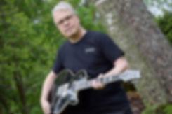 Taisto from Taisto Guitars with black AROK-FR Shadowman custom guitar