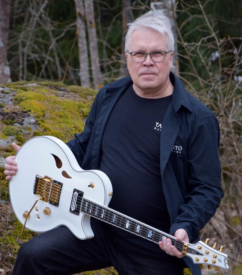 Taisto Heinonen with white Taisto Guitars AROK-FR Shadowman guitar