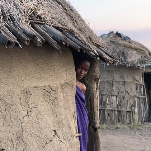 A Maasai woman standing in front of her hut in Mto wa Mbu, Tanzania
