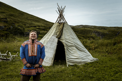 A Sami reindeer herder and a traditional tent