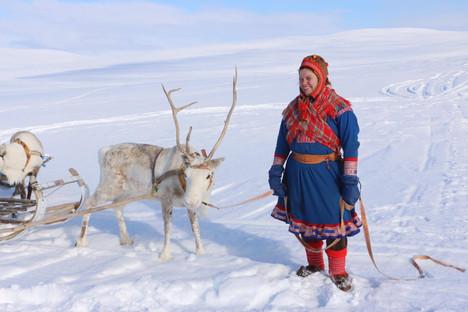 A Sami woman and a reindeer