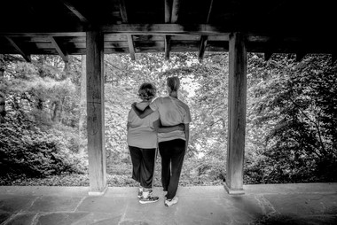 Image Description: A black and white photo of two women wearing black pants, white tshirts, and tennis shoes, standing on a porch looking out into a forest. They are facing away from the camera, their arms hugged around each others backs.