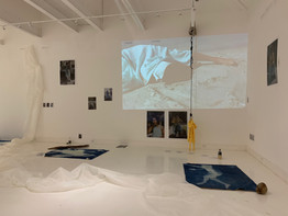"""Image Description: Photograph still of Gesel Mason's instillation, """"Josephine"""". A still image of video footage of Gesel laying on the beach is projected onto a white wall directly across from the camera. Hanging from the ceiling by black rope is a yellow raincoat. Images of Gesel in a flowy blue dress and black ankle boots are displayed on the white walls. Blue cynotype prints of Gesel's sillouette are scattered across the floor."""