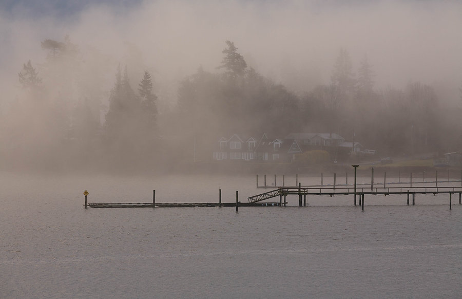 Wharf extends into Sooke Harbour on foggy day with house in background.