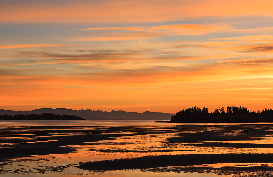Orange glowing sky and beach at Parksville sunrise.