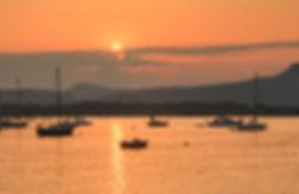 Sunset at Cowichan Bay with sailboats at anchor.