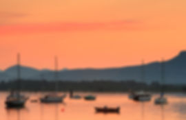 Glowing sky over sailboats at Cowichan Bay evening.