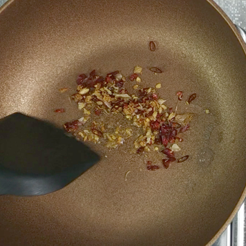 3. Place a wok on a medium heat. Once the wok hot add oil then dried garlic and if you like extra hot please add dried chili into the pan.