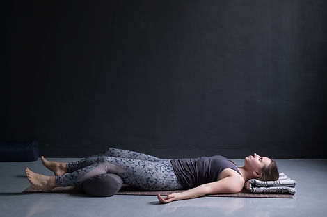 woman working out, doing yoga exercise on wooden floor, lying in Shavasana.jpg