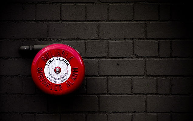 red fire alarm bell set against dark gre