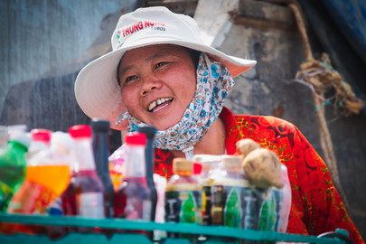 All she owns is a small wooden paddle boat full of drinks that she peddles all day around the floating market.