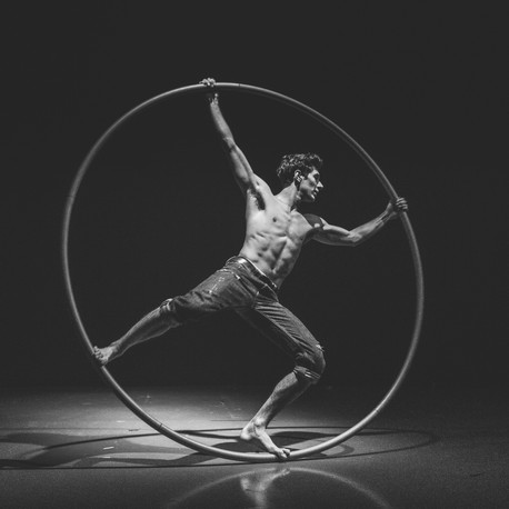 Man performing on a Cyr Wheel during a circus show in London, UK