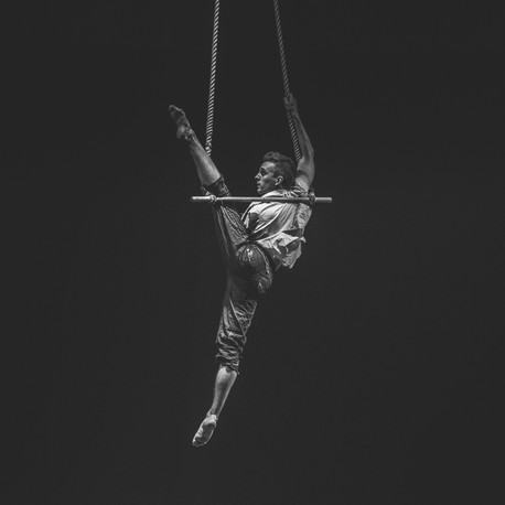 Man performing on Trapeze Bar during a circus show in London, UK
