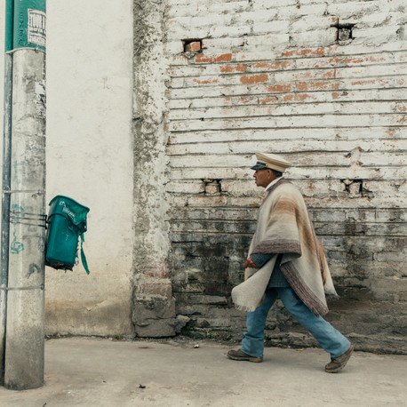 Man walking wearing a poncho and a hat. Colombia