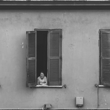 Woman staring out of the window. Rome, Italy