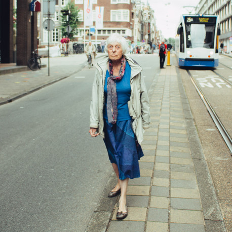 Woman in blue dress waiting for the tram in Amsterdam