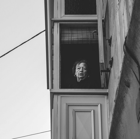 Woman staring out of the window. Gzira, Malta