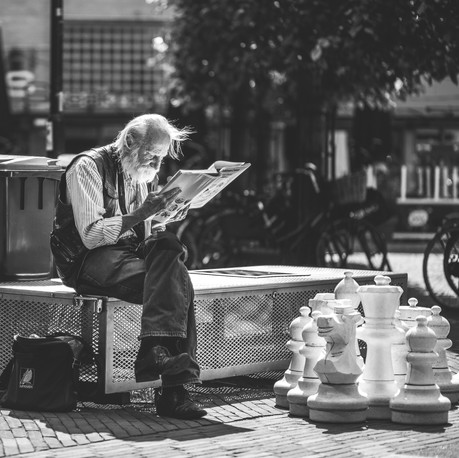 Man reading in front of giant chess board. Amsterdam, Netherlands