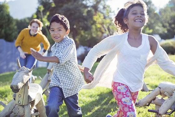 Lapset juoksevat puistossa.