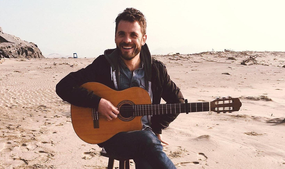 Ryan smiling with guitar on beach
