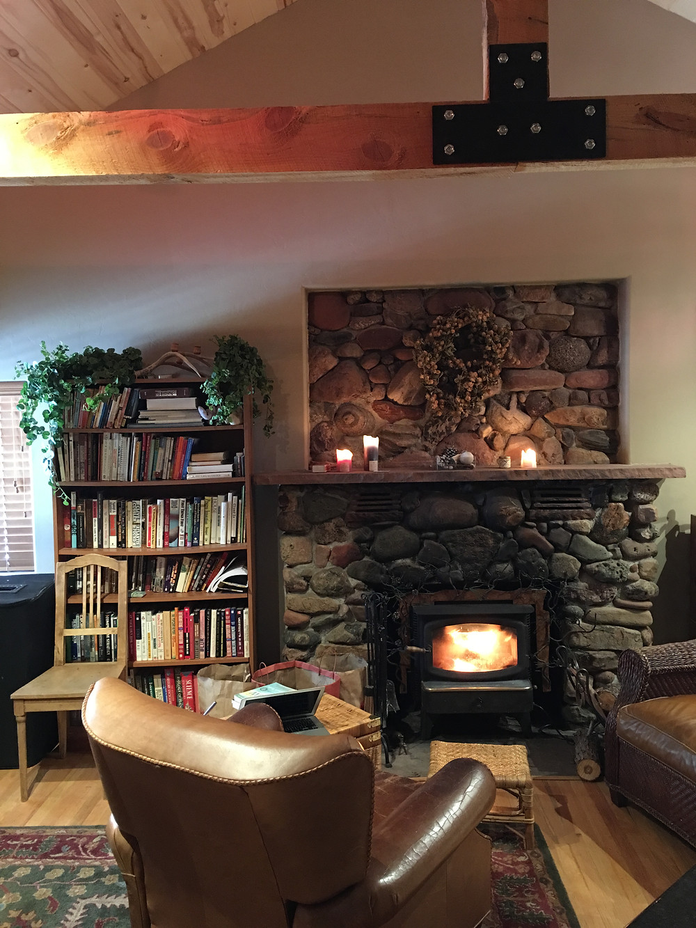 Inside Wheeling log-cabin surrounded by books, fire in the fireplace and leather chairs.
