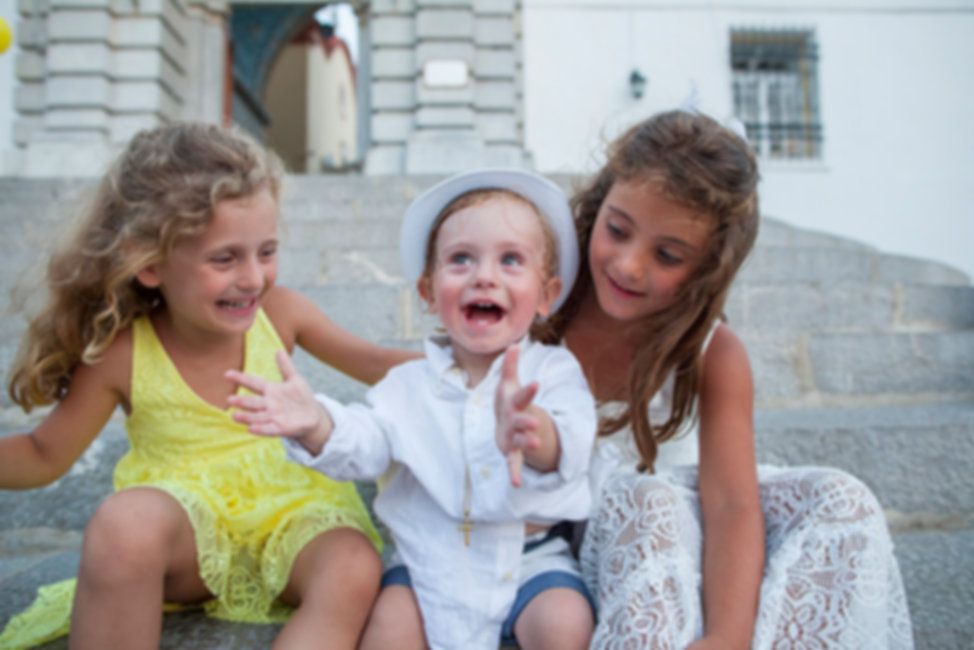 Two girls and a baby boy are having fun outside of the church. Photography Ioanna Chatzidiakou