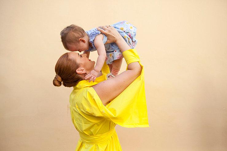 Φορωντας ενα κιτρινο φορεμα η μαμα σηκωνει το μωρο της ψηλα.