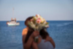 Best friend's strong hug to the bride. At the backround a boat at the sea
