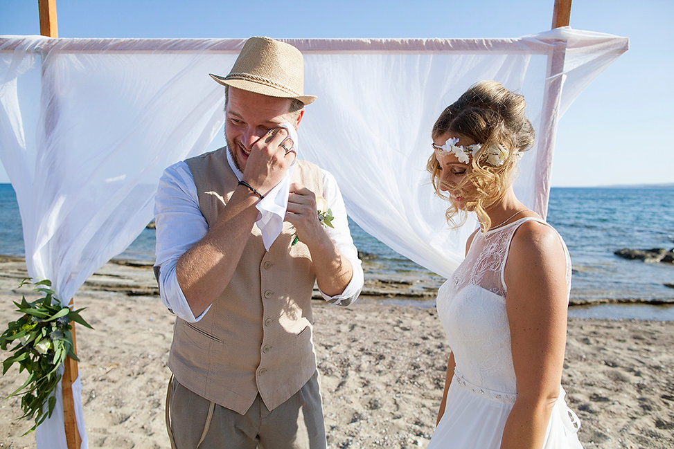 Wedding at the beach. The groom is wiping his tears.Photography Ioanna Chatzidiakou.