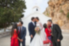 The bride, the groom and two more couples are kissing after the ceremony.