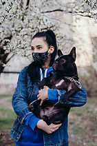 girl in a black mask with a dog on a bac