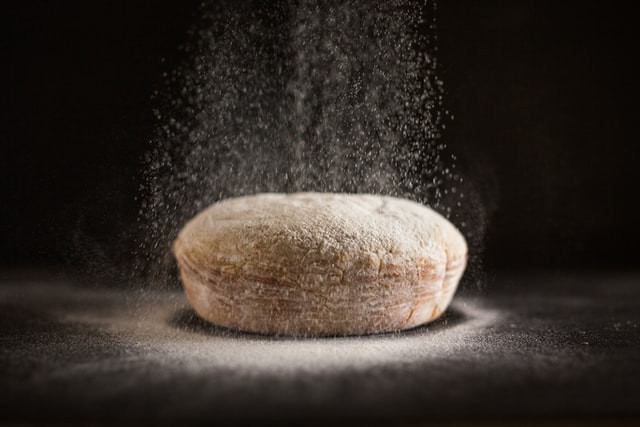 bread slicer bread sitting on dark table with dough pouring on it