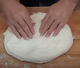 flattening a homemade bread sandiwch bread dough