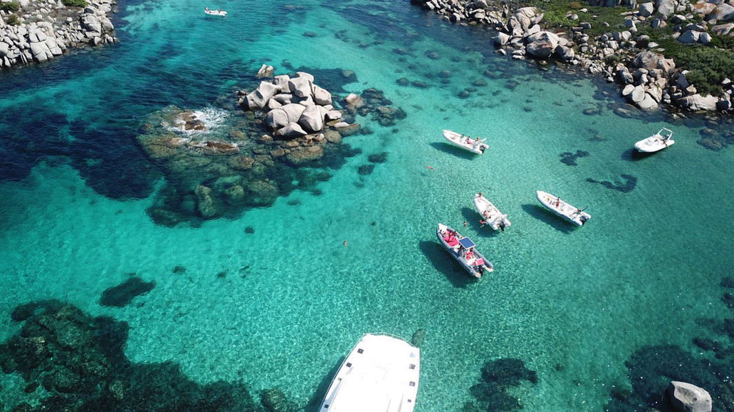 Aerial view in the turquoise sea of a lomac dinghy