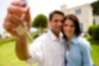 Home owners smiling holding house keys.