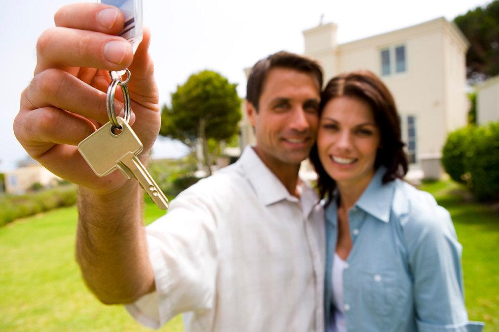 Casal com a chave da casa nova na mão