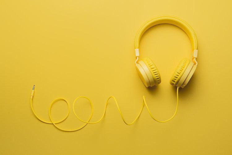 Yellow headphones on yellow background.