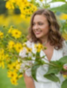 a girl posing for her senior sessionat Pebble Hall Wildflowers in Weyers Cave, VA