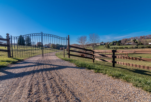 entrance to farm with rod iron double door gate and wooden horse fence