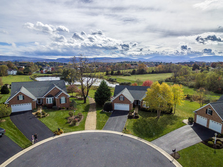 aerial shot of home with mountain views and lake on culdesac
