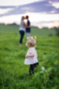 a child looking back at her parents on the farm
