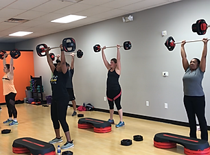 women lifting weights in group workout