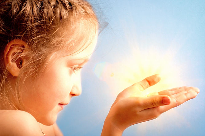 smiling child holding a sun at her hands on a blue sky background_edited.jpg