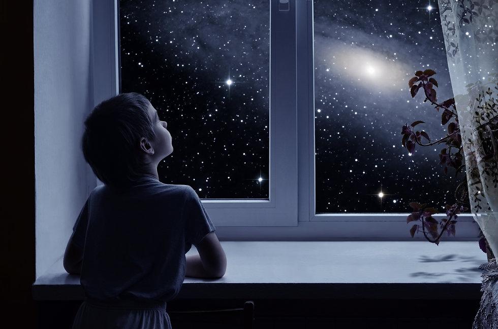 A little boy is standing near the window
