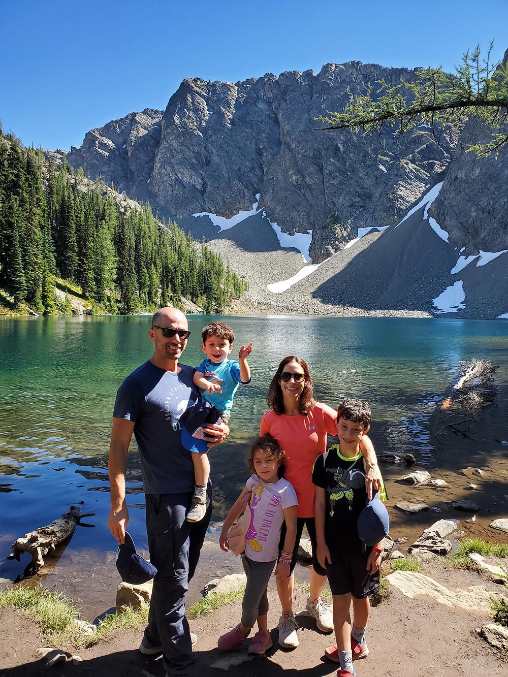 אישה, גבר, תינוק, בן ובת עומדים על רקע אגם בצבעי כחול וירוק וההרים עם שלג ברקע